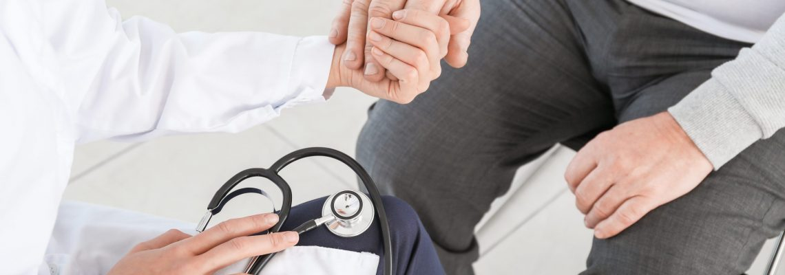 Female doctor with senior man suffering from Parkinson syndrome in clinic